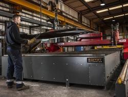 Loading a sheet of metal waiting to be cut on a plasma cutting bed