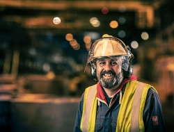 smiling Worker at Liberty Steel Newport with yellow hard hat and bib