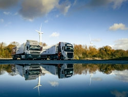 Trucks and wind turbine reflected in water at Liberty Steel Newport