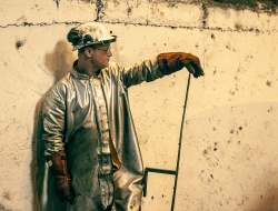 worker in protective silver suit at steel foundry