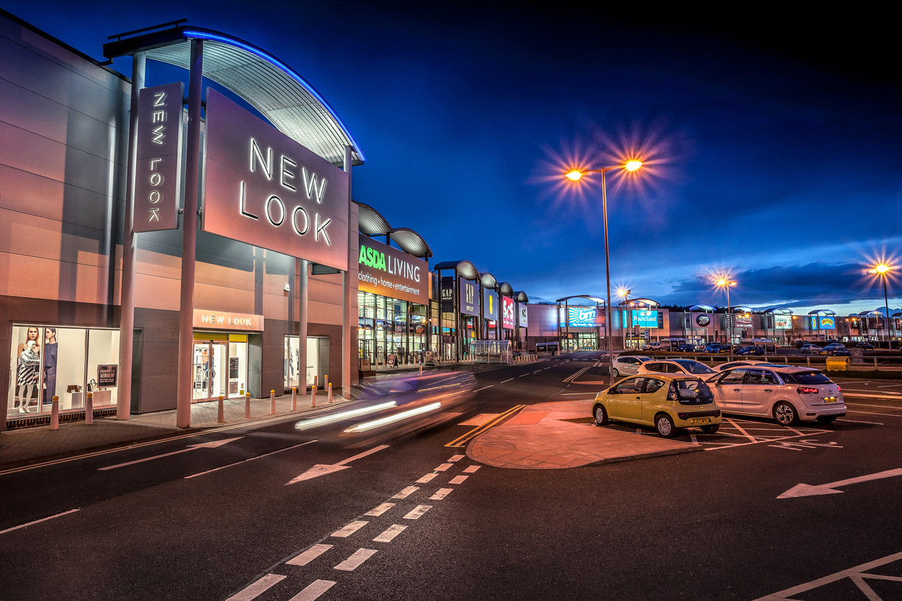 image New Look store and row of shops on team valley retail park gateshead at night with dark blue sky and tungsten lights