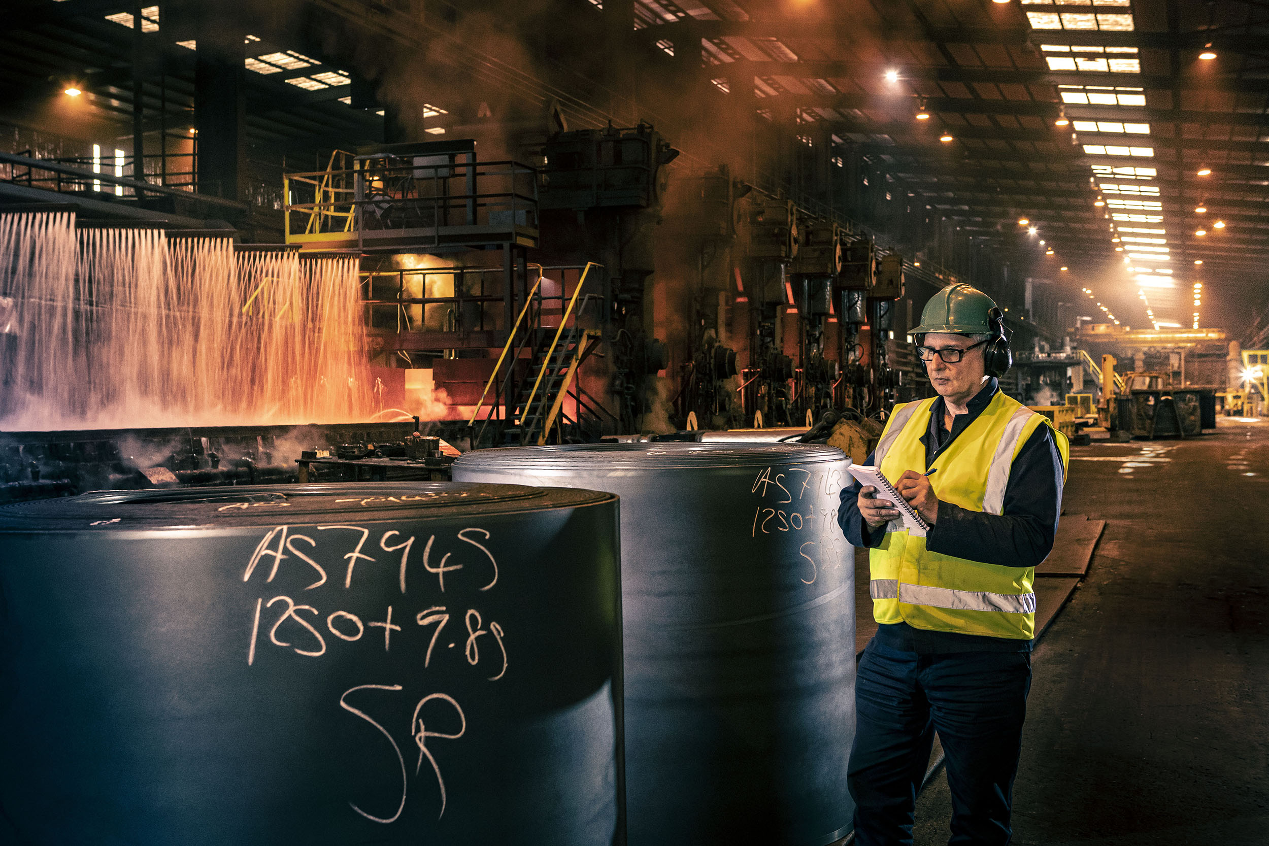 A man checking stock of steel coils in factory at Liberty Steel Newport Wales